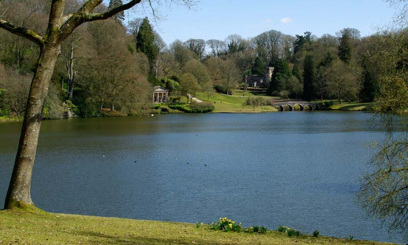 View across lake to Temple of Flora, the Palladian Bridge and St Peter's Church - Stourhead Gardens
